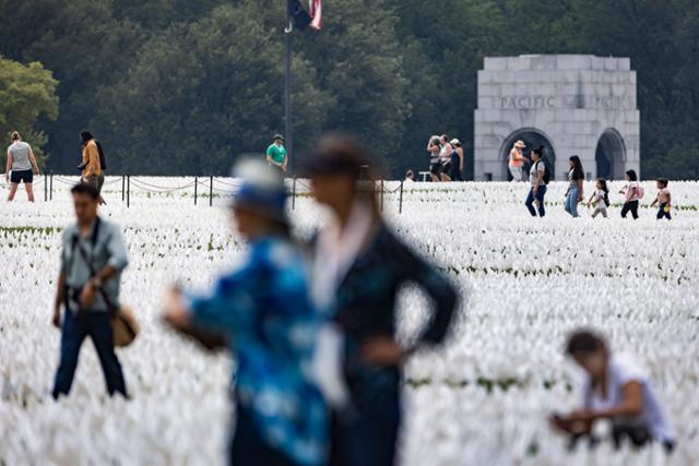 17일 설치미술 작품 '미국에서:기억하라'가 설치된 미국 워싱턴 내셔널 몰을 찾은 시민들이 코로나19 희생자들을 추모하고 있다. 워싱턴=EPA 연합뉴스