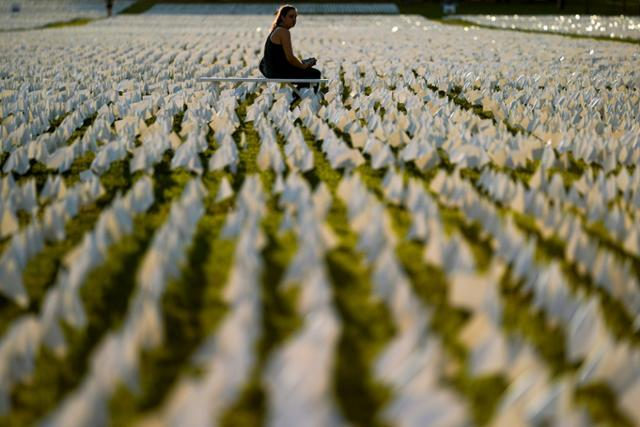 한 시민이 17일 설치미술 작품 '미국에서:기억하라'가 설치된 미국 워싱턴 내셔널 몰을 찾아 코로나19 희생자들을 추모하고 있다. 워싱턴=AP 연합뉴스
