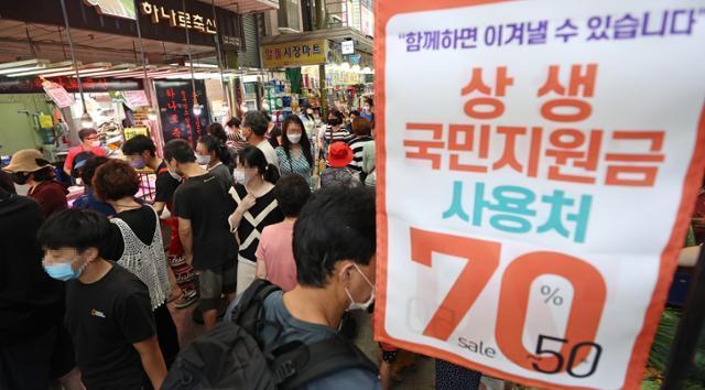 추석 전날인 지난 20일 오후 서울 망원시장의 한 점포에 국민지원금 이용 가능 안내문이 붙어 있다. 연합뉴스
