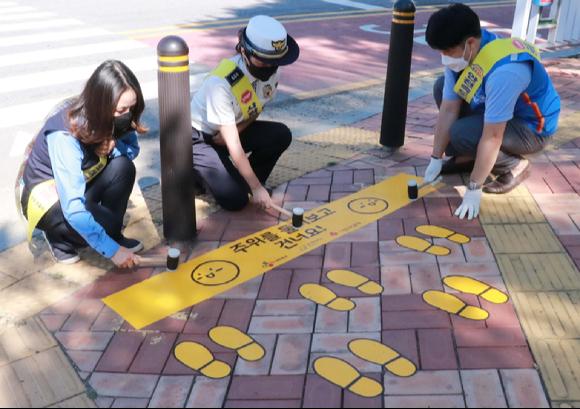 CJ대한통운이 경기도 군포시 어린이보호구역에 노란발자국을 설치하고 있다. [사진=CJ대한통운]